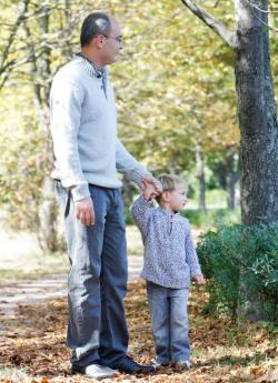 dad holding son's hand in autumn setting