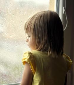 little girl looks out of rainy window
