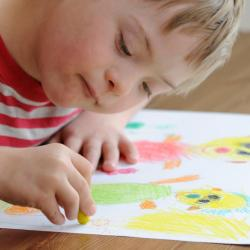 young boy with down syndrome painting