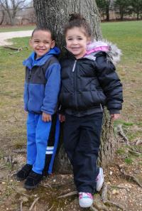 Two children standing by a tree smiling