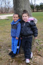 two children smiling leaning against a tree