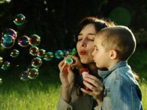 boy blowing bubbles with young mum