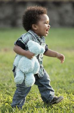 toddler with teddy bear on field
