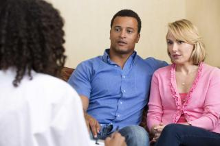 Couple on sofa being spoken to by a social worker