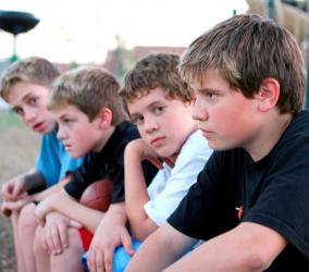four teenage boys sitting outdoors