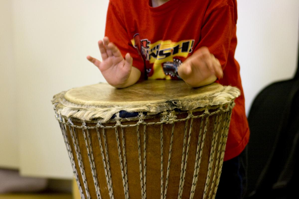Young child expresses himself through drums in music therapy