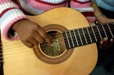 child's hands in guitar
