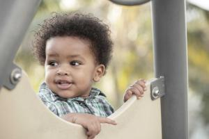 Black toddler playing outdoors on play structure