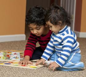 two adopted boys playing on carpet