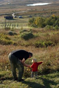 man with toddler in field