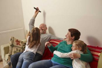 Mum, dad and adopted daughters playing on sofa