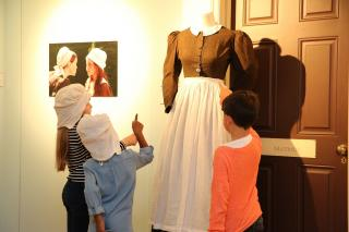 Children looking at Foundling Hospital uniforms in an interactive exhibit