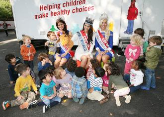 Miss World with children having a healthy living lesson from Coram children's charity