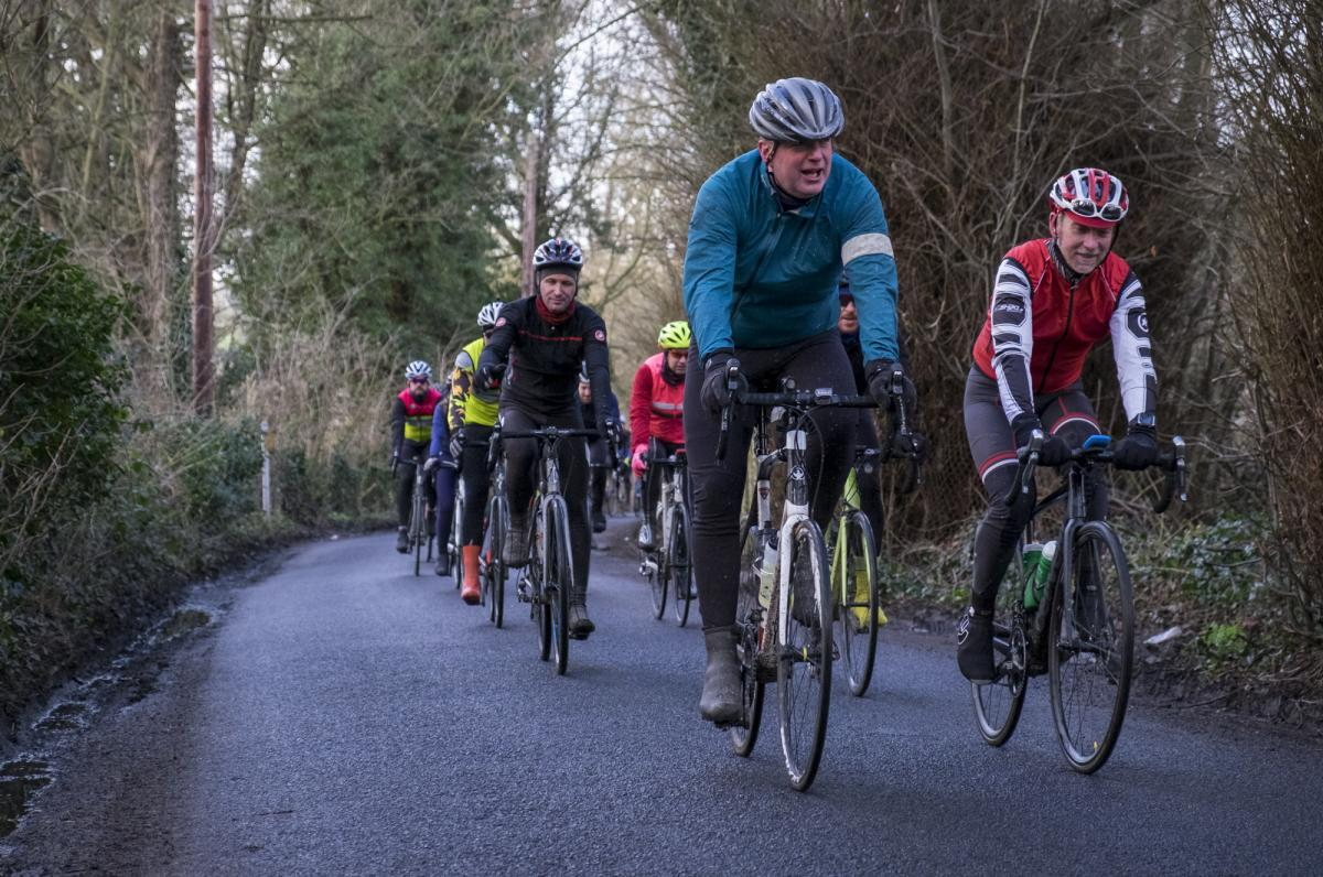 Riders cycling down a country lane