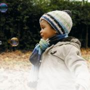 Black boy playing in park blowing bubbles
