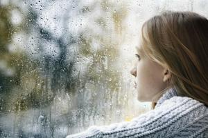 Girl in care looking out of the window at rainy scene