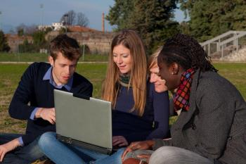 Group of teenagers sitting in a park around a laptop computer
