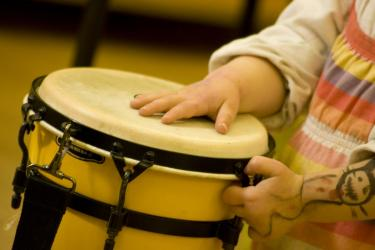 young child drums in music therapy