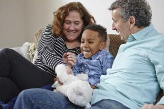 Mum, dad, little boy on sofa with toy