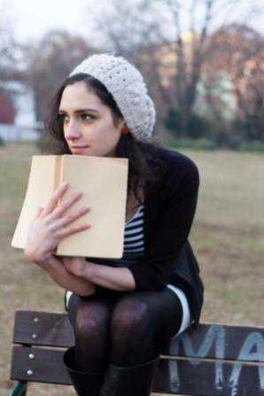 Teenage girl sitting on park bench holding a book