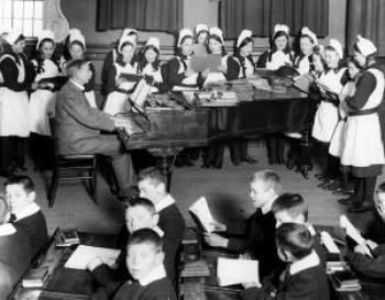 Foundling children singing around a piano