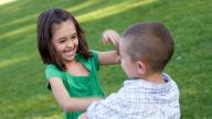 young white boy and girl play fighting in grass