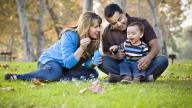 Ethnically diverse parents on grass with baby boy blowing bubbles