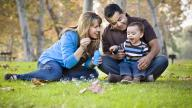 Parents playing with their adopted child in the park