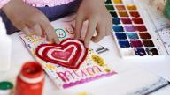 Adopted daughter - girl's hands making I love mum card