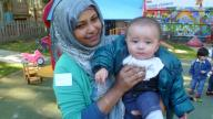 Volunteer with baby at Coram Parents' Centre