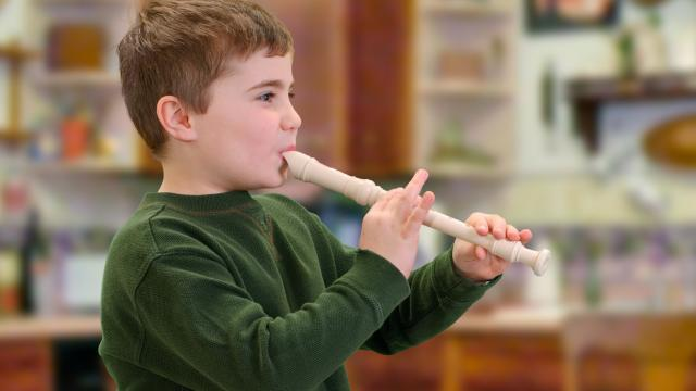 A young boy plays the recorder