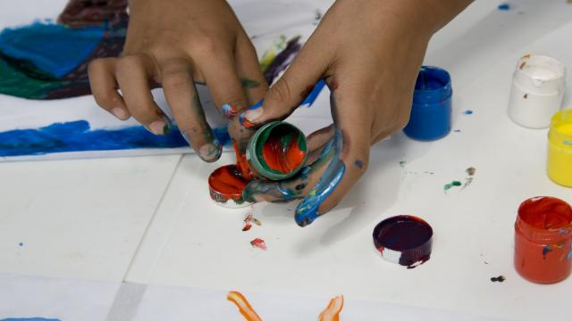 Child finger painting in art therapy