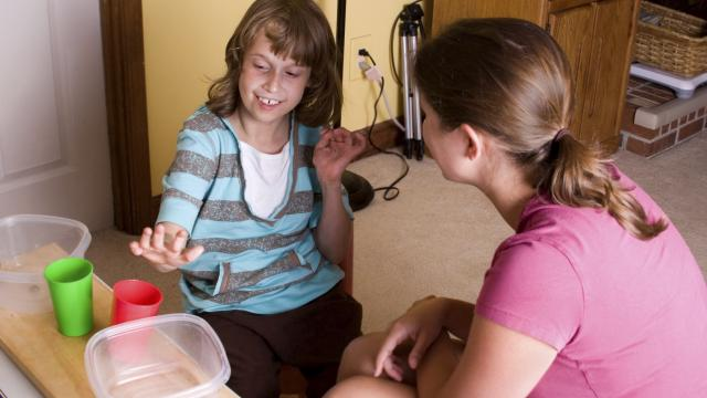 autistic girl sitting in home setting with woman