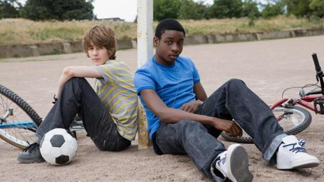 Two teenage boys sitting on ground with a bike