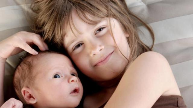 Girl cuddling young baby