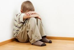 Boy in corner of a room with his head in his arms